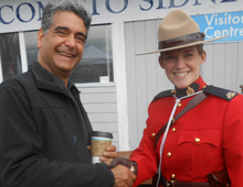 Friday Harbor Town Council member Farhad Ghatan visits with Mountie Jessica, who is on hand to welcome the first ferry of the season.