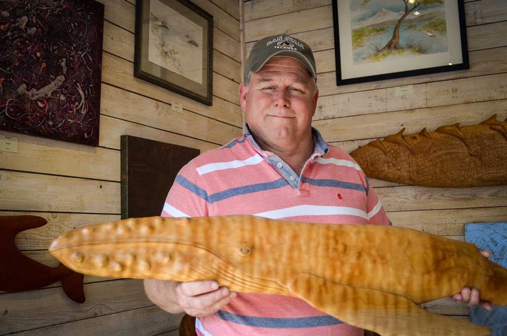 """Artist Terry Ogle with his  work, """"Tiger Striped Humpback"""", a carving of Quilted Western Maple local to the island - Tim Dustrude photo"""