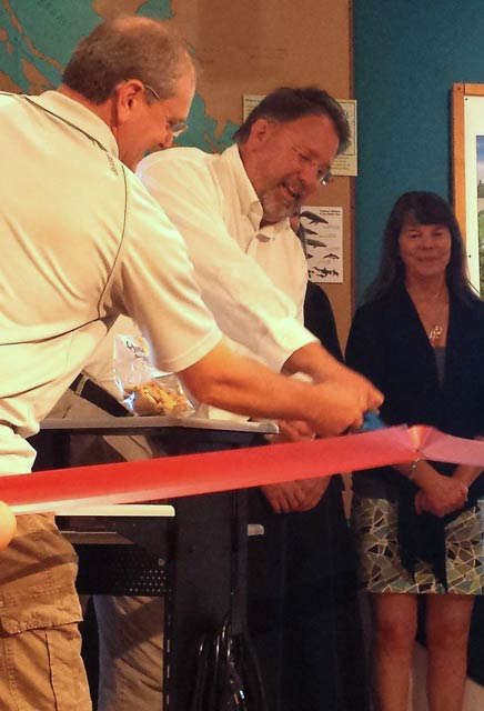 Mike Martin assists Duncan Wilson while Rebecca Parks (hidden) and Cynthia Burke stand by at the ribbon cutting launch of Whale Tale Cookies at the San Juan Island Whale Museum - Contributed photo