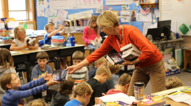 Rotary member, Cyndy Gilason hands out books to happy children - Ted Strutz photo
